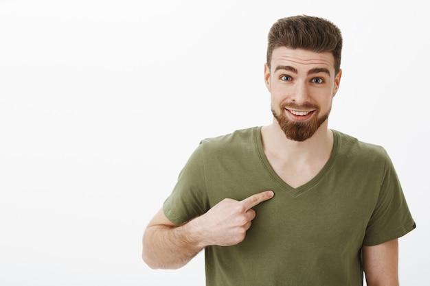 Ja naprawdę poważnie. zaskoczony szczęśliwy i zachwycony mężczyzna wskazujący na siebie trzymający palec wskazujący skierowany na klatkę piersiową zadający pytanie z radosnym uśmiechem