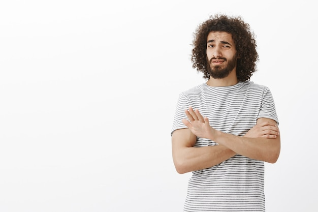 """Ja tego nie kupuję. portret niewzruszonego, nielubianego atrakcyjnego faceta ze wschodu z kręconymi włosami i brodą w koszuli w paski, skrzyżowanymi rękami i pokazującym dłoń w geście """"nie"""" lub """"stop"""""""