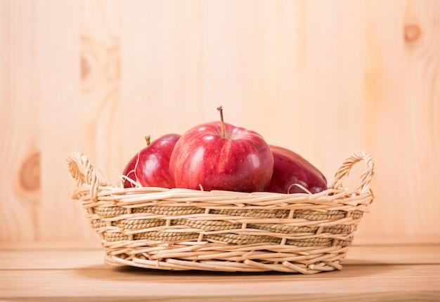 Jabłczana czerwień na koszu z drewnianą podłoga