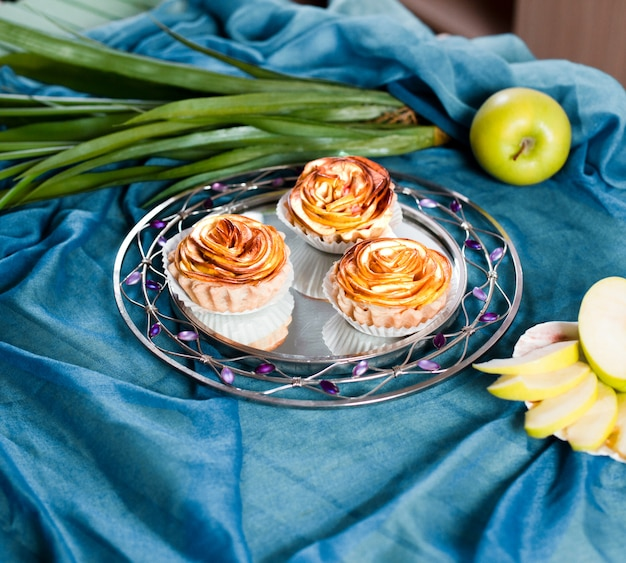 Jabłczane słodkie placki w kształcie kwiatu w talerzu.