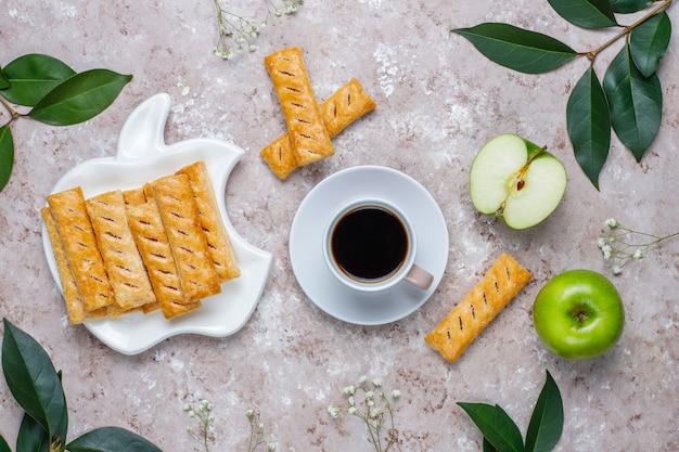 Jabłczani ptysiowego ciasta ciastka w jabłczanym kształta talerzu z świeżymi jabłkami, odgórny widok