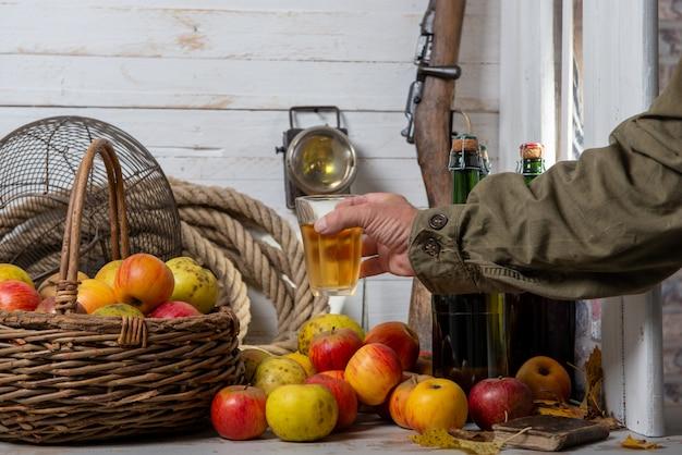 Jabłka ekologiczne z mężczyzną do picia szklankę pyszne francuskiego cydru
