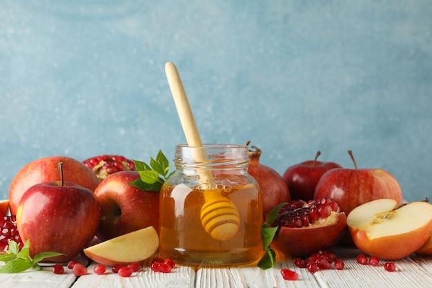 Jabłka, granatowiec i miód na drewnianym stole, zamykają up