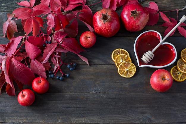 Jabłka, granaty, plasterki cytryny, miód w wazonie
