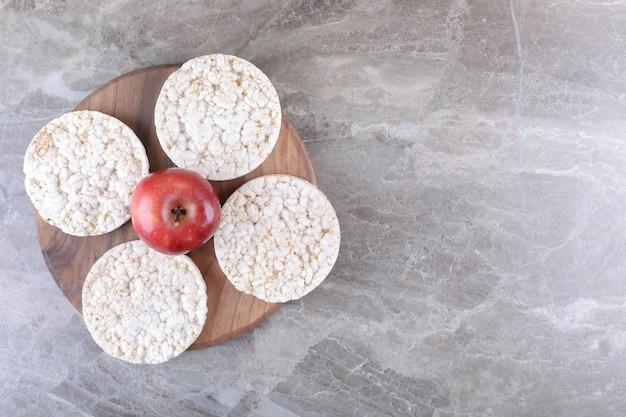 Jabłka i ciastka ryżowe dmuchane na drewnianej tacy, na marmurowej powierzchni