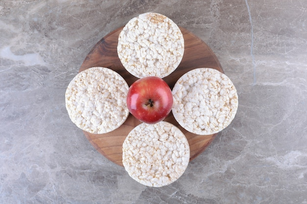 Jabłka i ciastka ryżowe dmuchane na drewnianej tacy, na tle marmuru.