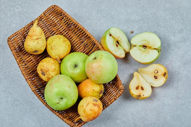 Jabłka i gruszki na koszu na szaro.