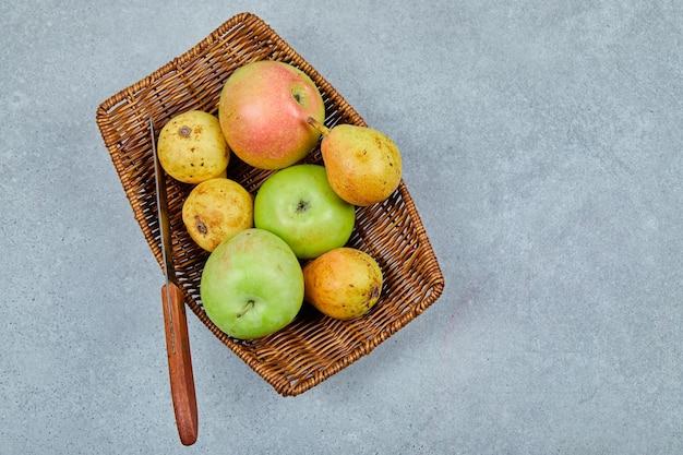 Jabłka i gruszki na koszu z nożem.