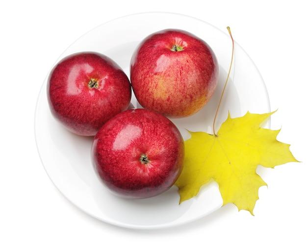 Jabłka i liście klonu w talerzu na białym