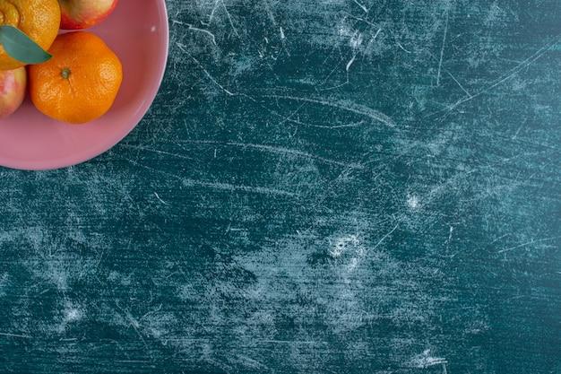 Jabłka i mandarynki na talerzu, na marmurowym stole.