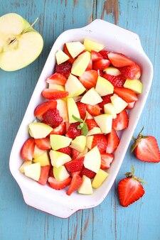 Jabłka i plasterki truskawek w naczyniu do pieczenia
