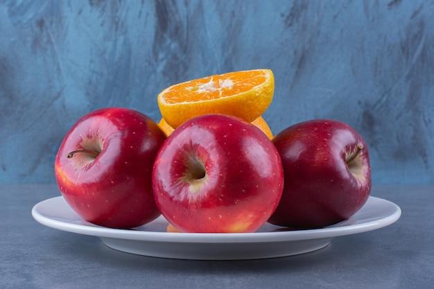 Jabłka i pomarańcza na talerzu na ciemnej powierzchni