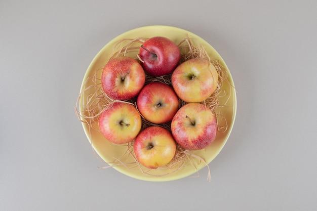 Jabłka i słoma w misce na marmurze