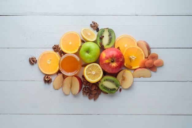 Jabłka, kiwi, suszone owoce, pomarańcze i jabłka. koncepcja zdrowego odżywiania. strzał na białym drewnianym stole.