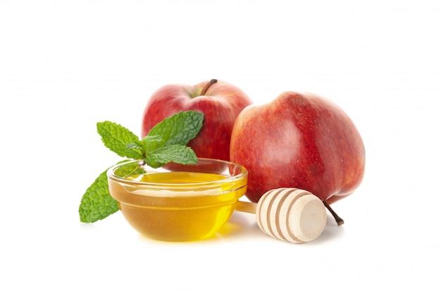 Jabłka, miód i mennica odizolowywający na bielu. naturalne leczenie