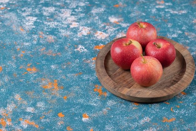 Jabłka na białym tle na rustykalną drewnianą deską do krojenia