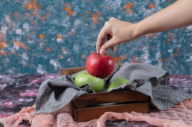 Jabłka na rustykalnej drewnianej tacy na teksturowanej.