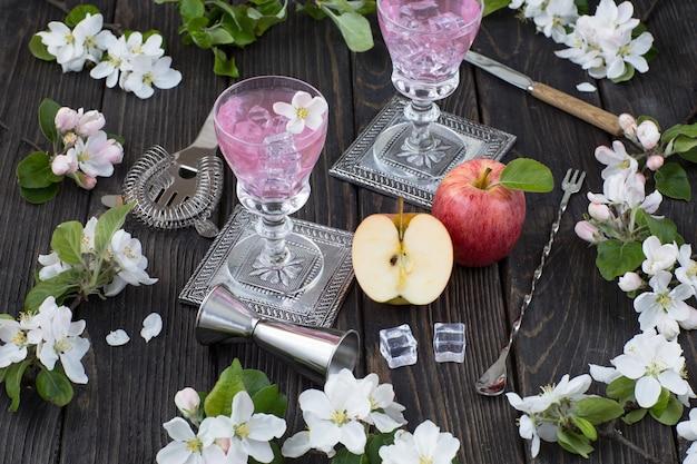Jabłka, napój w szklankach, przedmioty do robienia koktajlu i gałęzie kwitnącej jabłoni na drewnianym stole