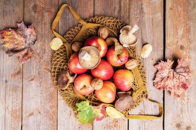 Jabłka, orzechy włoskie, grzyby cardoncelli spadają do bawełnianej torby eko z siatki i pozostawiają na starych drewnianych deskach. jesienne zakupy, żniwa, zero odpadów