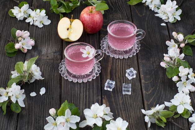 Jabłka, pić w kubkach i gałęziach kwitnącej jabłoni na drewnianym stole