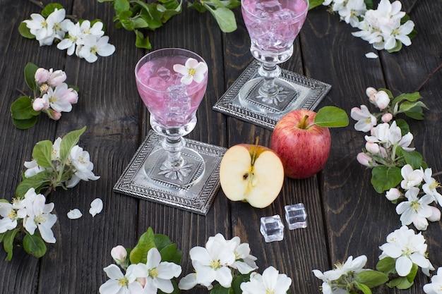 Jabłka, pić w szklankach i gałęzi kwitnących jabłoni na drewnianym stole