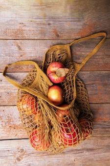 Jabłka spadają do bawełnianej torby z siatki i liści na starych drewnianych deskach. jesienne zakupy, żniwa, zero odpadów