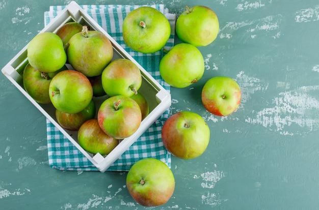 Jabłka w drewnianym pudełku leżały płasko na tle tynku i tkaniny piknikowej