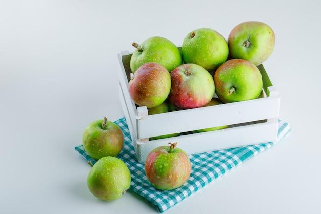 Jabłka w drewnianym pudełku na białej i piknikowej szmatce. wysoki kąt widzenia.