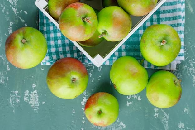 Jabłka w drewnianym pudełku na tle tkaniny piknikowej i tynku. leżał płasko.