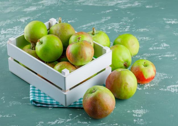 Jabłka w drewnianym pudełku na tle tkaniny piknikowej i tynku. wysoki kąt widzenia.