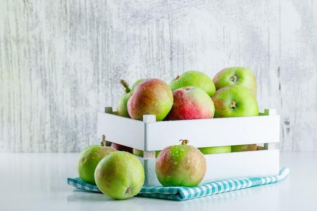 Jabłka w drewnianym pudełku z widokiem z boku tkaniny piknikowej na białym i nieczysty