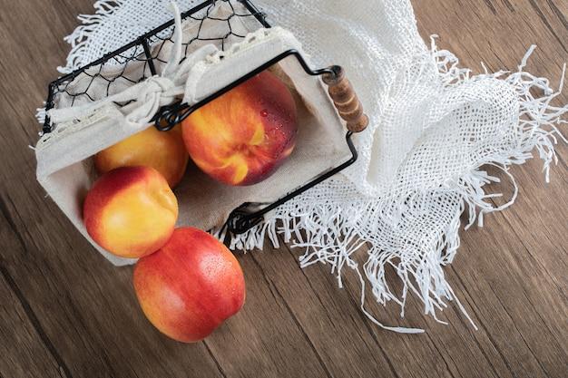 Jabłka w koszu na białym ręczniku na stole.