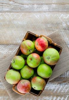 Jabłka w koszu na drewnianej i podkładce, widok z góry.