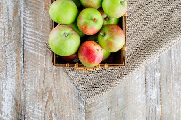 Jabłka w koszu na drewnianej i podkładce