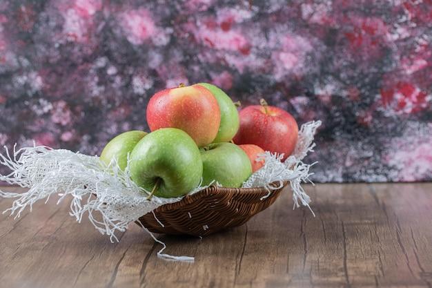 Jabłka w koszu na kawałku białego juta.