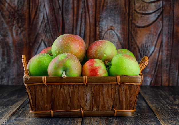 Jabłka w koszu na starym drewnianym tle. widok z boku.