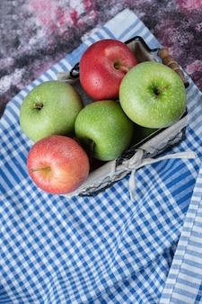 Jabłka w koszu pokrytym białym ręcznikiem.