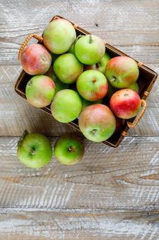 Jabłka w koszyku widok z góry na drewno
