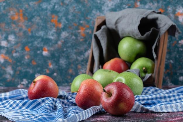 Jabłka w rustykalnej drewnianej tacy na ręczniku kuchennym