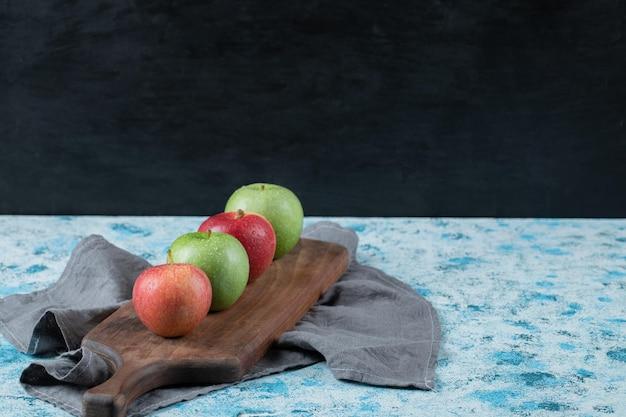 Jabłka w rzędzie na wąskiej desce.