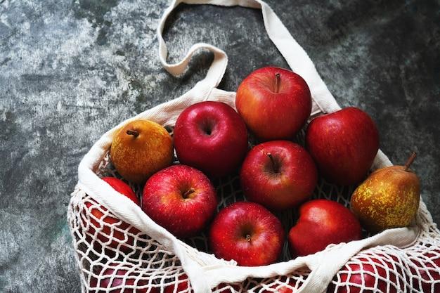 Jabłka w siatkowej torbie nad stołem. zrównoważony rozwój i świadoma koncepcja konsumpcji. widok z góry. flat lay