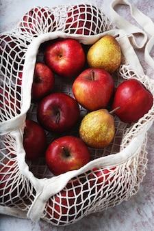 Jabłka w siatkowej torbie. zrównoważony rozwój i świadoma koncepcja konsumpcji. widok z góry. flat lay