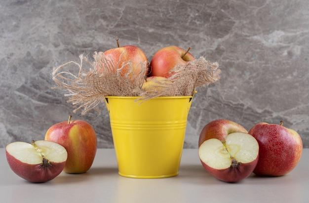 Jabłka w środku i obok małego wiaderka na marmurze