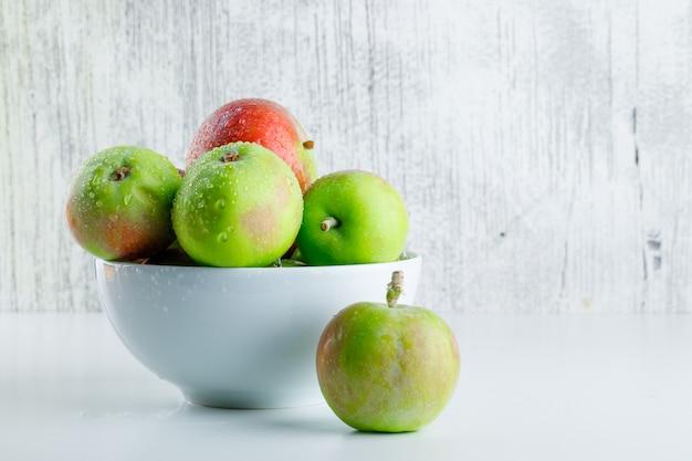 Jabłka w widoku z boku miski na białym i nieczysty