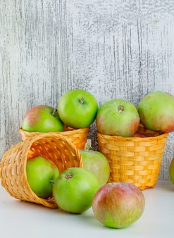 Jabłka w wiklinowych koszach widok z boku na biały i nieczysty
