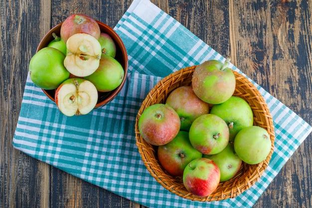 Jabłka w wiklinowym koszu i miski na tle tkaniny drewniane i piknik. widok z góry.