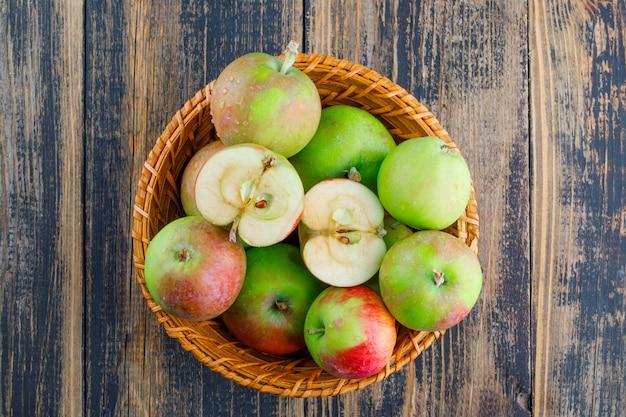 Jabłka w wiklinowym koszu na drewnianym tle. leżał płasko.