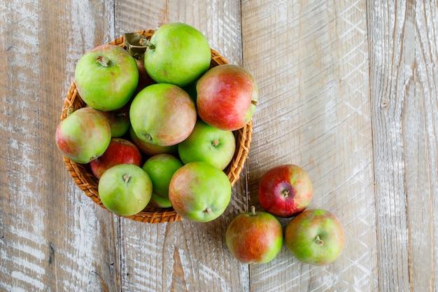 Jabłka w wiklinowym koszu na drewnie.