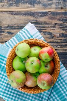 Jabłka w wiklinowym koszu na tle tkaniny drewniane i piknik. widok z góry.