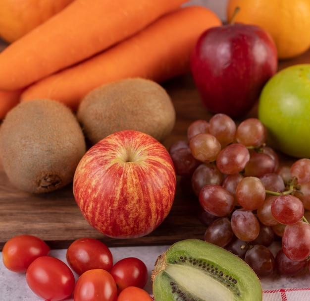 Jabłka, winogrona, marchewki i pomarańcze ułożone razem na ziemi.